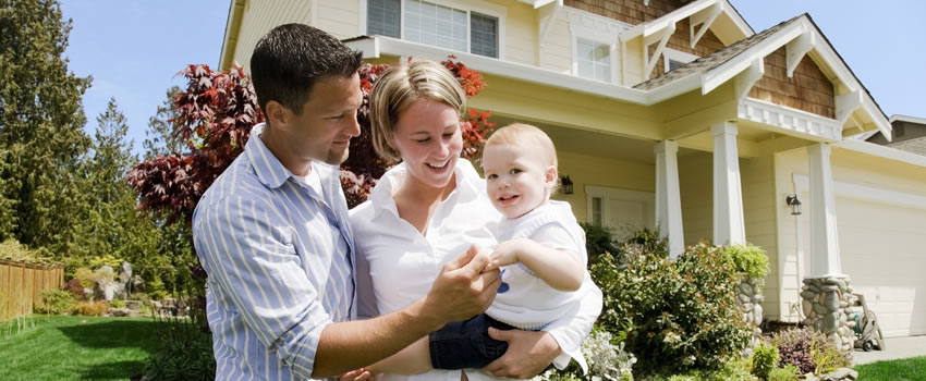 family with baby in front of house
