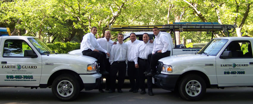pest professionals at Earth Guard with white service trucks